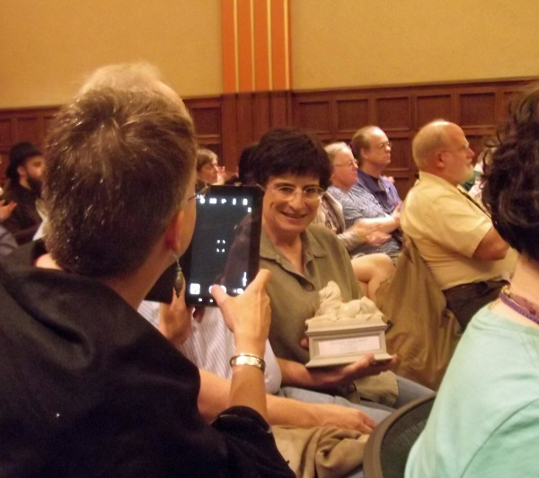 Susan Palwick uses her iPad to take a photo of Lisa Goldstein with her Mythopoeic Fantasy Award lion statuette, at the Mythcon 43 post-banquet award presentations. (Photo by Lynn Maudlin)